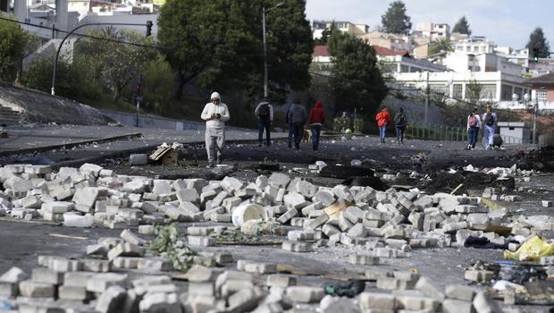 Pedestrians walk through the debris of barricades set by anti-government demonstrators (Fernando Vergara/AP)