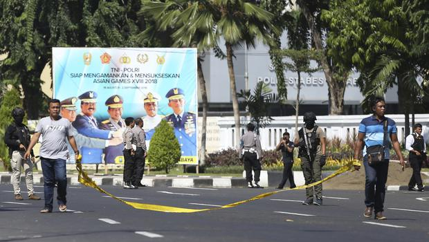 Officers set up a police line outside the local police headquarters following an attack in Surabaya (Achmad Ibrahim/AP)