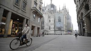 A cyclist pedals in a deserted street in Milan, Italy (Luca Bruno/AP)