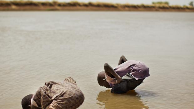 Children drink water from the Sobat River in the Greater Upper Nile region of northeastern South Sudan (Julien Behal/PA)