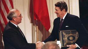 US president Ronald Reagan, right, shakes hands with Soviet leader Mikhail Gorbachev after the leaders signed the Intermediate Range Nuclear Forces Treaty in 1987 (AP)