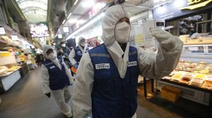 Workers arrive to spray disinfectant at a market in Seoul, South Korea (Ahn Young-joon/AP)