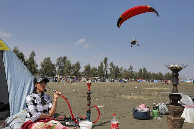 A woman smokes a water pipe as a motorised paraglider flies on the annual public picnic day on the 13th and last day of the Persian New Year, or Nowruz, holiday at Gisoum beach near the city of Talesh, in northern Gilan province, Iran (Ebrahim Noroozi/AP)