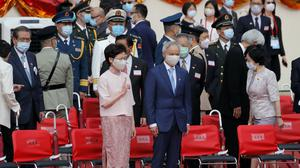 Hong Kong Chief Executive Carrie Lam, left, and her husband Lam Siu-por attend the flag raising ceremony at the Golden Bauhinia Square to mark the anniversary of the Hong Kong handover to China (Kin Cheung/AP)