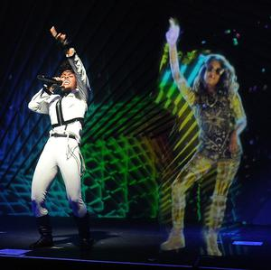 Janelle Monae performs alongside holograms of MIA during a launch party for the Audi M3 (AP)