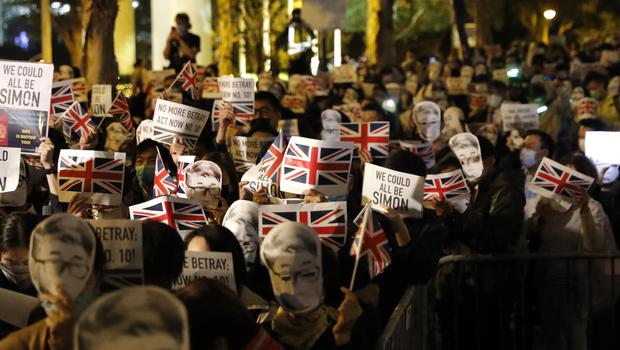 Protesters wear masks of Simon Cheng, a Hong Kong British Consulate employee, as they gather for a rally outside the British Consulate in Hong Kong (Vincent Thian/AP)