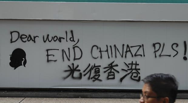 A man walks past a wall with the words Liberate Hong Kong- Dear World End Chinazi Please in Hong Kong (Vincent Yu/AP)