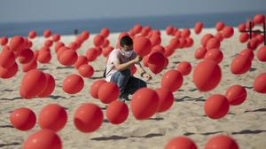 A man places red balloons in the sand on Copacabana beach (Mario Lobao/AP)