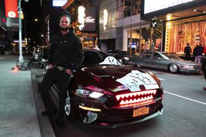 Andre Godfrey with his 2018 Ford Mustang EcoBoost – with glowing red shark teeth embedded in the grill – in Times Square (Mark Lennihan/AP)