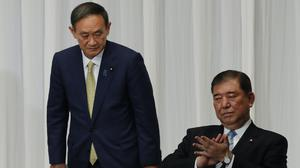 Japanese chief cabinet secretary Yoshihide Suga, left, and former defence minister Shigeru Ishiba attend a speech session for the Liberal Democratic Party's (LDP) leadership election at its headquarters in Tokyo (Kim Kyung-hoon/Pool Photo via AP)
