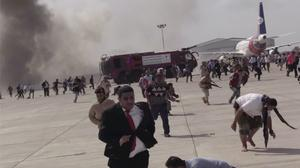 People run after an explosion at the airport in Aden, Yemen (AP)