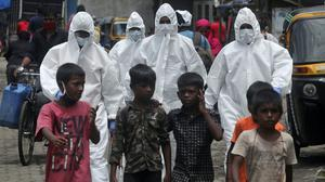 Health workers wearing protective clothing arrive to screen people for Covid-19 symptoms at a slum in Mumbai (Rafiq Maqbool/AP)