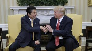 US president Donald Trump shakes hands with Japanese prime minister Shinzo Abe in the Oval Office (AP/Evan Vucci)