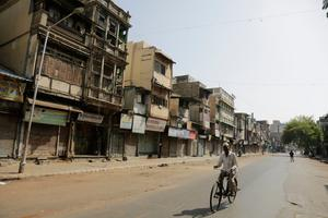An Indian man rides a bike on an empty street in Ahmedabad