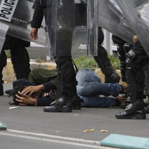 Riot police detain a protester during a mass eviction of striking teachers from the Zocalo, Mexico City's main plaza (AP/ Marco Ugarte)