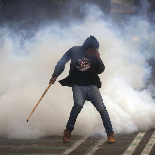 A protester is overcome by tear gas near the Zocalo plaza in Mexico City (AP/Christian Palma)