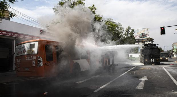 A police water cannon extinguishes a burning bus that was set alight by demonstrators during a protest in Santiago, Chile, Saturday, Oct. 19, 2019. The protests started on Friday afternoon when high school students flooded subway stations, jumping turnstiles, dodging fares and vandalizing stations as part of protests against a fare hike, but by nightfall had extended throughout Santiago with students setting up barricades and fires at the entrances to subway stations, forcing President Sebastian Pinera to announce a state of emergency and deploy the armed forces into the streets. (AP Photo/Esteban Felix)