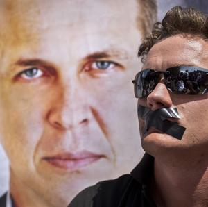 A protester sits next to a banner showing detained Al-Jazeera journalist Peter Greste (AP Photo/Ben Curtis)