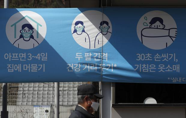 A man wearing a face mask as a precaution against coronavirus walks past a banner at a park in Seoul, South Korea (Lee Jin-man/AP)
