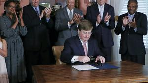 Mississippi Republican Governor Tate Reeves gathers the pens he used in signing the bill retiring the last state flag in the United States with the Confederate battle emblem (Rogelio V. Solis/AP, Pool)