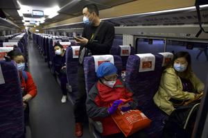 Passengers wearing face mask on the first high-speed train to leave Hankou railway station after the resumption of train services in Wuhan (Ng Han Guan/AP)
