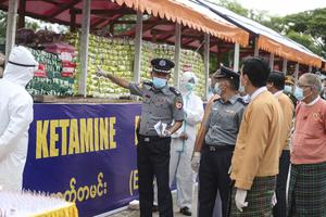 A police officer explains about seized illegal drugs to Yangon Region Chief Minister Phyo Min Thein (Thein Zaw/AP)