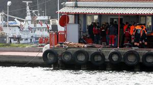 Dead bodies covered with blankets lie on the ground after a boat carrying suspected migrants from Afghanistan and Syria sank just north of the Bosphorus Strait (AP)