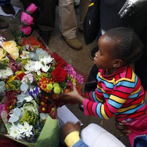 An unidentified young girl lays flowers outside the hospital (AP)