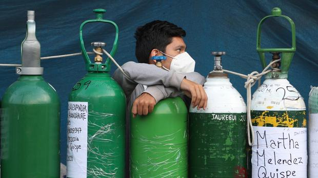 A youth rests on his empty oxygen cylinder waiting for a refill shop to open in Lima, Peru (Martin Mejia/AP)