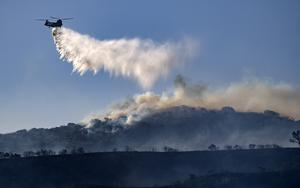 A helicopter drops retardant on the Silverado wildfire (Mindy Schauer/The Orange County Register/AP)
