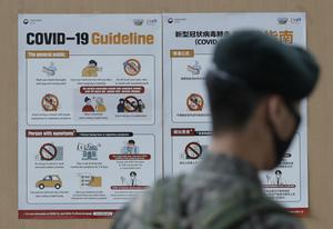 A South Korean soldier wearing a face mask walks near banners showing precautions against the new coronavirus in Seoul (Lee Jin-Man/AP)