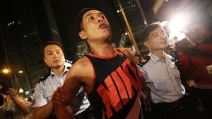 Local police take a man away from a confrontation between pro-democracy student protesters and angry local residents in Kowloon's Mong Kok district (AP)