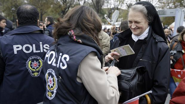 A police officer checks the bag of a Catholic nun ahead of Pope Francis' visit to Haghia Sofia