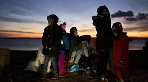 Migrants sit on a bench after their arrival from Turkey at the shores of the Greek island of Chios (AP)