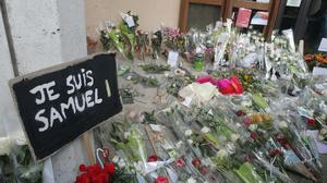 A poster reading 'I am Samuel' and flowers lie outside the school in Conflans-Sainte-Honorine, north-west of Paris, where the murdered teacher had been working (Michel Euler/AP)