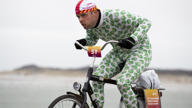 A competitor wearing a onesie with Brussels sprouts battles gale-force winds during the Dutch Headwind Cycling Championships (Peter Dejong/AP)
