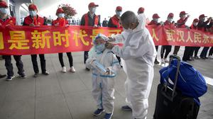Travellers wearing face masks and suits to protect against the spread of new coronavirus walk past people holding a celebratory banner at Wuhan Tianhe International Airport i(Ng Han Guan/AP)