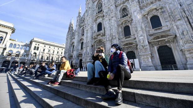 People wearing sanitary masks sits in front of the Duomo gothic cathedral, in Milan, Italy, Monday, Feb. 24, 2020. At least 190 people in Italy's north have tested positive for the COVID-19 virus and four people have died, including an 84-year-old man who died overnight in Bergamo, the Lombardy regional government reported. (Claudio Furlan/Lapresse via AP)