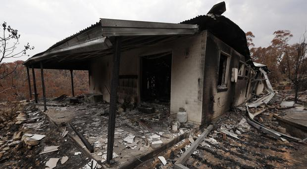The home of Justin Kam and Helena Wong barely stands after a fire destroyed the house at Balmoral, Australia, (Rick Rycroft/AP)