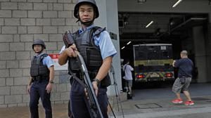 Police officers stand guard next to a prison bus which carries British banker Rurik Jutting upon his arrival at the High Court in Hong Kong (AP)