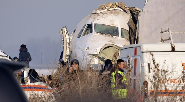 Police and investigators at the scene of the crash near Almaty airport in Kazakhstan (Vladimir Tretyakov/AP)