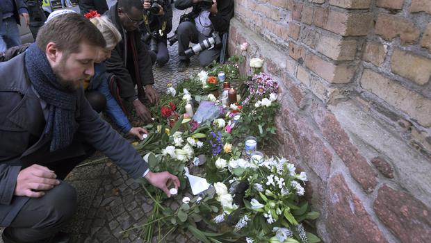 People place flowers outside the synagogue targeted in the attack (Jens Meyer/AP)