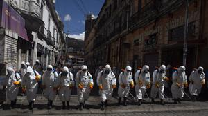Workers fumigate a street to help contain the spread of Covid-19 in La Paz, Bolivia (Juan Karita/AP)