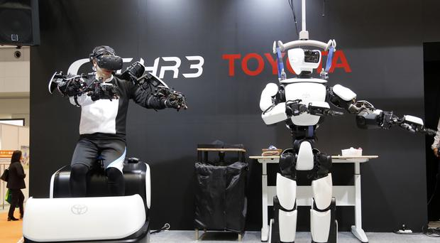 The T-HR3 robot, right, is remotely controlled by its staff member, left (AP)