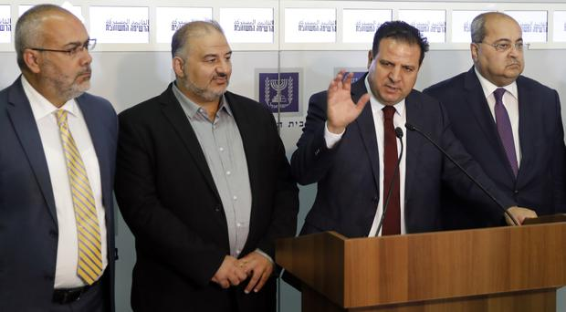 Members of the Joint List, Ayman Odeh, centre, Ahmad Tibi, right, Osama Saadi, left, and Mansour Abbas, second left, speak to the press (Menahem Kahana/Pool/AP)