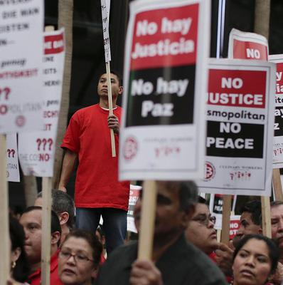 Culinary Union workers watch as fellow workers sit on Las Vegas Boulevard outside the Cosmopolitan Hotel and Casino (AP/Julie Jacobson)