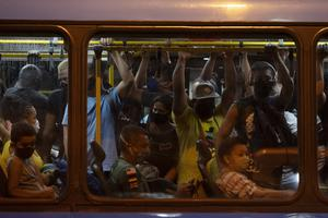 Commuters wearing protective face masks ride a bus amid the new coronavirus pandemic in Rio de Janeiro (AP)