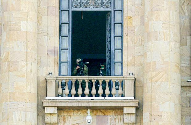 A security agent points a sniper rifle from a window of the parliament building in Yerevan (Hrant Khachatryan/PAN Photo via AP)