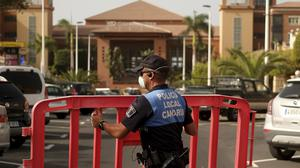 A Spanish police officer sets a barrier blocking the access to the H10 Costa Adeje Palace hotel in Tenerife (AP)