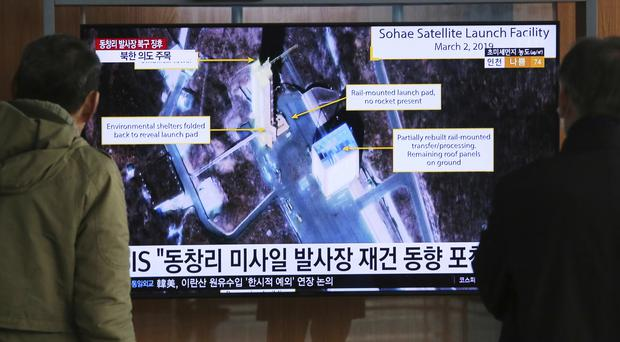 People watch a TV screen showing an image of the Sohae Satellite Launching Station in Tongchang-ri, North Korea (Ahn Young-joon/AP)